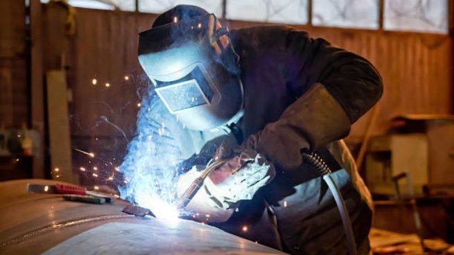 Obrero soldando con su máscara de protección